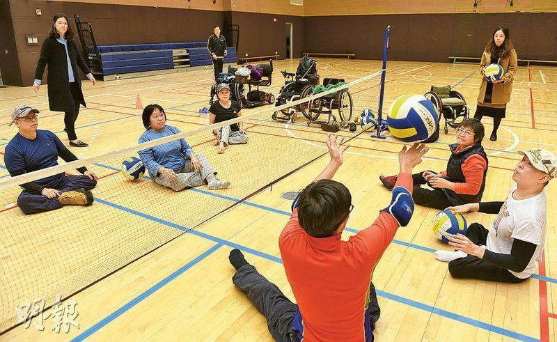 輕排球重約100至150克,較傳統排球的260至280克輕;圓周則約80至83厘米,比傳統排球的65至67厘米大。圖為多名肢體殘疾人士坐地玩輕排球,網高跟從坐地排球標準,男子和男女混合賽為1.15米,女子賽事則為1.05米。小兒麻痺症患者鍾綺華(遠方戴帽女士)認為,輕排球較輕,又不需用輪椅,容易入門。(劉焌陶攝)