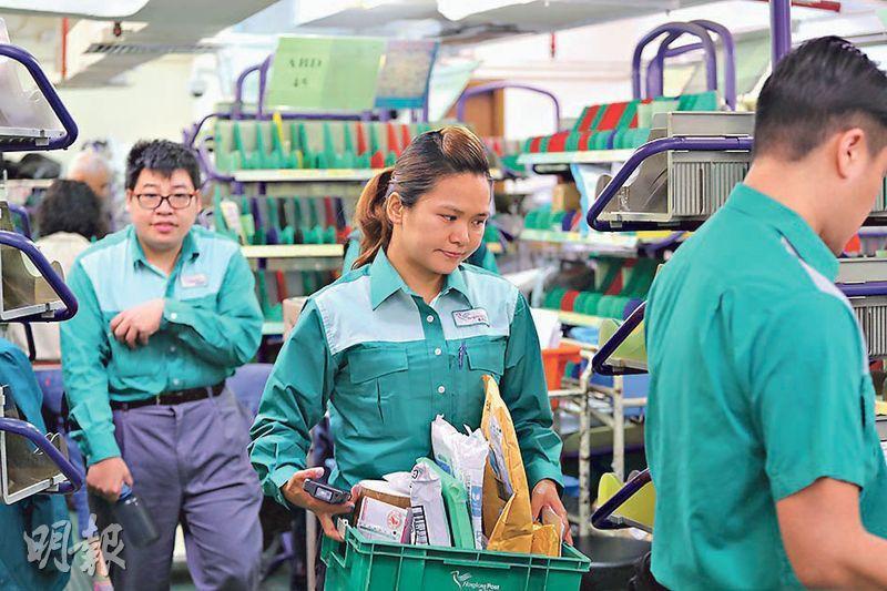 劉錄霞是香港仔派遞局內唯一女郵差,體力不亞於男同事,能輕鬆抬起一籃籃郵件,年輕時更能一口氣揹起3個各重16公斤的郵袋。(李紹昌攝)