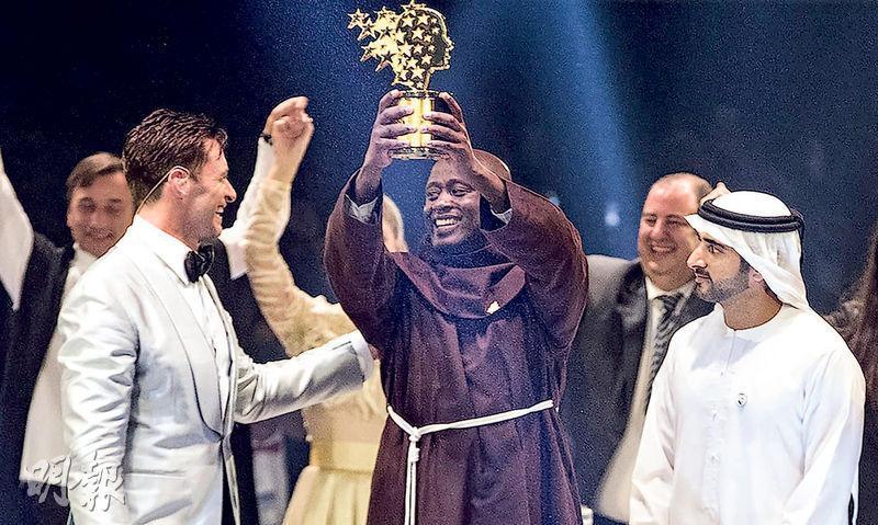 在肯尼亞偏遠村莊教學的方濟會修士塔比希(中)高舉「全球教師獎」獎座。(法新社)