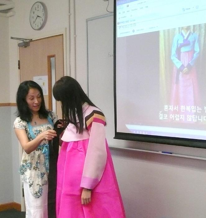 要學好語言,培養興趣、語境是重要的關鍵。修讀者可透過參加不同國家的文化體驗活動,認識有關地道文化,發掘學習的樂趣,有助延續學習的決心。圖為韓語導師教導學員穿著韓服的技巧。(相片由香港浸會大學持續教育學院提供)