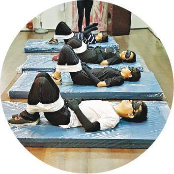 體驗被縛——何琴在假期時自行到台灣參觀當地「自立支援學院」,看到其他人正在參加「被縛」體驗活動,讓參加者感受長者被縛的不安。(受訪者提供)