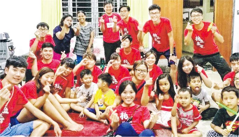 陳念瑩(最前排中)讀三年級時,與其他宿生組成義工隊。她帶香港同學回家鄉馬來西亞行善,一行人帶備衣物、食米等日常物資,探訪當地居民。(受訪者提供)