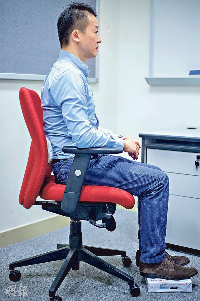 要自製「人體工學辦公椅」,鄭樹基表示可把浴巾充當背墊,加上自製腳踏,讓腰脊與腿部約呈100度,這樣脊椎便可保持天然弧度。(林靄怡攝)
