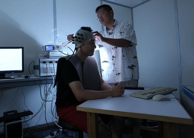 生物醫學工程結合了生命與科技,圖為蘇孝宇教授 (圖右) 利用近紅外光譜系統來量度大腦反應。(圖由受訪者提供)