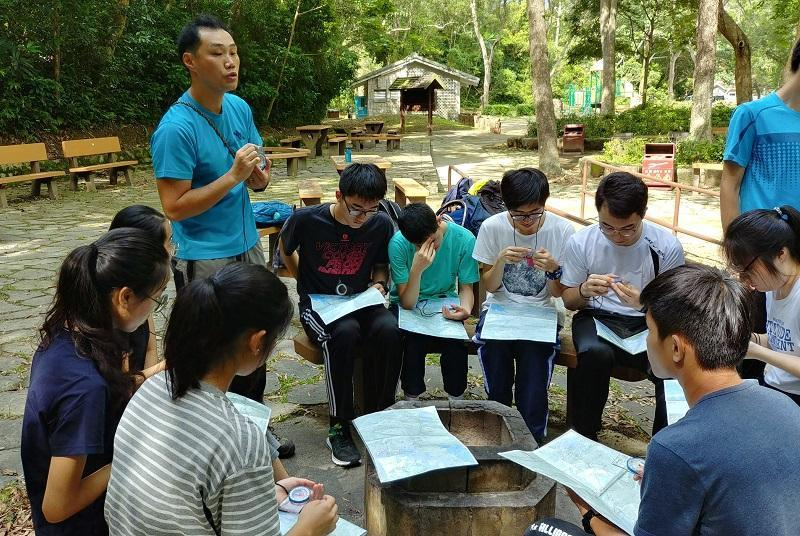 山藝教練工作充滿挑戰。圖為山藝教練教授使用地圖指南針等技巧。(圖由中國香港攀山及攀登總會提供)