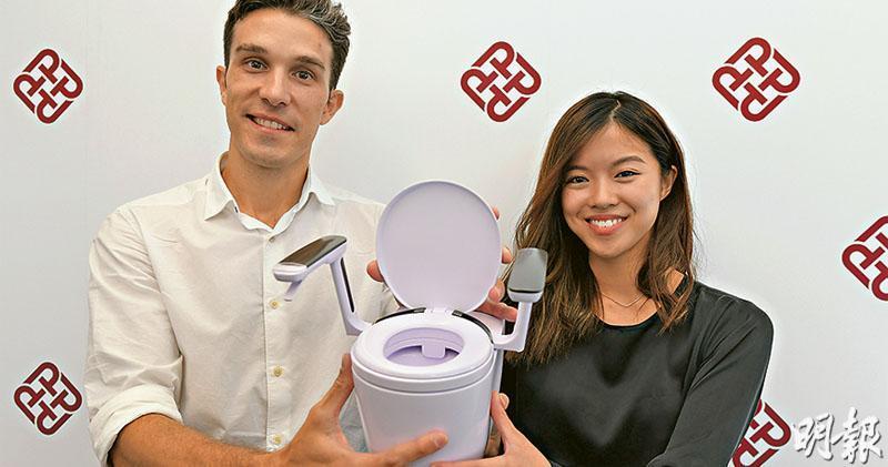 理大資助初創企業Studio Doozy,創辦人鄧曉瑩(右)和Joan Calduch(左)研發的坐廁(二人手上為模型)可安裝有扶手的旋轉廁板,方便行動不便或輪椅者坐上。鄧說扶手上有裝置可檢測如廁者的健康數據。(鍾林枝攝)