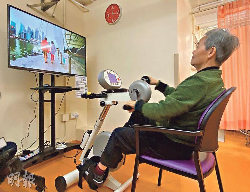 虛擬實境健身單車接駁熒幕後,用家可選擇「遊覽」169條世界各地路線,成為耆康會啟業護理安老院中最受歡迎設施。71歲院友熊月嫻(圖)使用健身單車後,由原本要坐輪椅改善到可用步行架走路。(林穎茵攝)