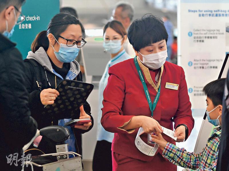 國泰航空昨日表示,鼓勵所有員工放3周無薪假。圖為國泰職員協助旅客辦理登機手續。(資料圖片)