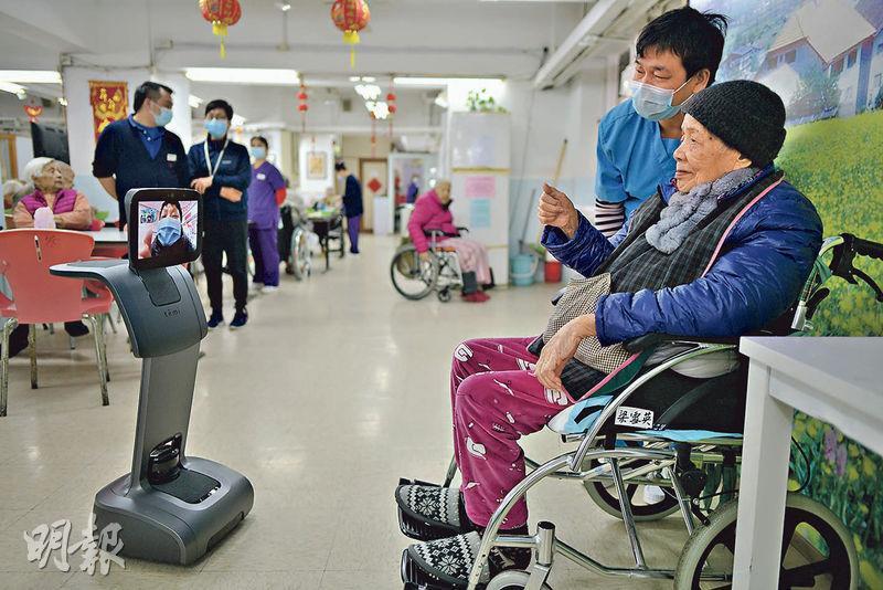 武漢肺炎肆虐,西環一間護老院縮短探訪時間,年屆102歲高齡的梁雪英(坐輪椅者),透過護老院新引入的機械人與家人視像會面。(鍾林枝攝)