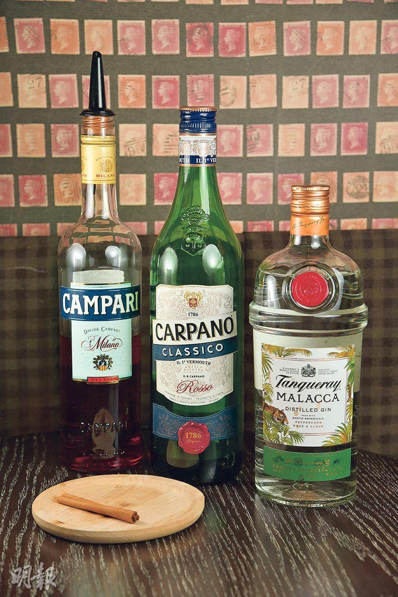 煙熏肉桂Negroni製作步驟 1. 材料——Davide Campari-Milano Bitter(金巴利苦味酒)、Carpano Classico Rosso(卡波諾經典苦艾酒)、Tanqueray Malacca Distilled Gin(添加利馬六甲蒸餾氈酒)、肉桂棒(黃志東攝)