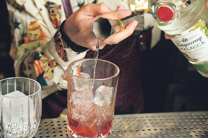 煙熏肉桂Negroni製作步驟 2. 調酒——先拿出要飲用的酒杯和調酒用的杯,並將冰塊分別加進兩個杯內。將3種酒以1:1:1的比例倒進調酒杯(圖中示範為20:20:20毫升),並攪拌至完全混合。加入酒品時不分先後次序,喜歡味道濃烈一點的話可將分量增加至30:30:30毫升(黃志東攝)