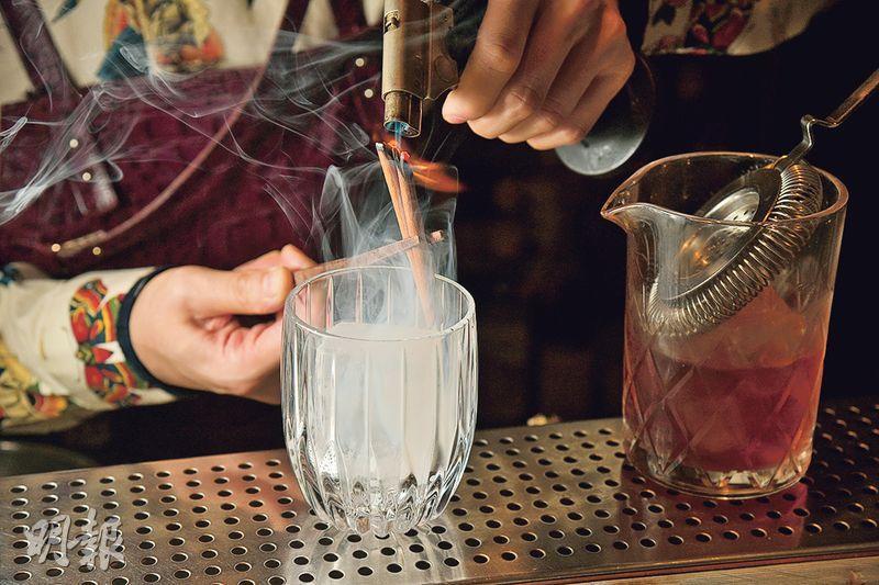 煙熏肉桂Negroni製作步驟 3. 燒肉桂棒——將肉桂棒對準酒杯內的冰塊,用火槍灼燒肉桂棒的另一端,讓香氣慢慢煙熏進冰塊中。燒的時間愈長,冰塊所散發的肉桂味道便更強(黃志東攝)