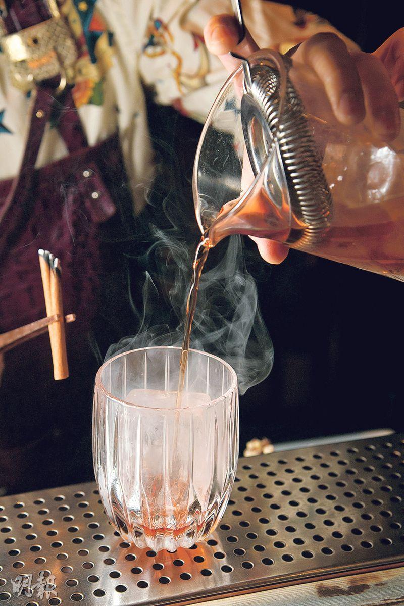 煙熏肉桂Negroni製作步驟 4. 倒酒——將已調好的酒倒進酒杯(黃志東攝)