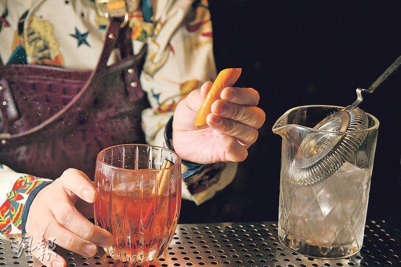 煙熏肉桂Negroni製作步驟 5. 裝飾——將燒完的肉桂棒放進酒內,可以增加肉桂的香氣和點綴完成品,另外亦可放上橙皮作裝飾(黃志東攝)