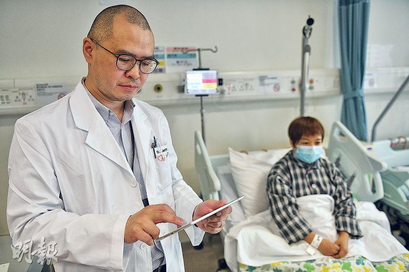 天水圍醫院急症科顧問醫生黎靖匡(左)3年前開始使用平板電腦,代替於病房內用「枱頭機」瀏覽病人資料。他表示,用平板電腦可「一站式」看到病人及病人牌板,不用為了查資料而來回穿梭病房。(林靄怡攝)