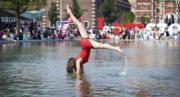 在荷蘭阿姆斯特丹,女子在噴泉打起筋斗,展示另一種泡水解暑方法。(法新社)