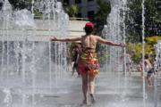 在法國巴黎,噴泉成為民眾消暑好地方。(法新社)