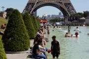 法國巴黎不少民眾坐在水池邊消暑。(法新社)