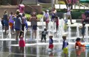 在加州洛杉磯,大人小朋友齊齊到公園水池玩水。(法新社)