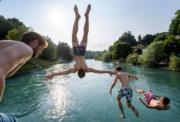 在瑞士首都伯恩,有男士跳進河中嬉水。(法新社)