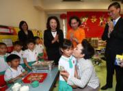 6月29日,國家主席習近平夫人彭麗媛(前右)參觀又一村學校,吻謝向她致送紀念品的小女生。(政府新聞處facebook圖片)