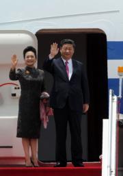 7月1日,國家主席習近平(右)與夫人彭麗媛(左)結束訪港行程,彭麗媛穿上一襲棕色旗袍。(法新社)