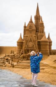 沙雕城堡造工精細,遊人拍照留念。(法新社)