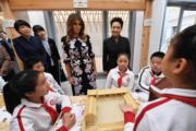 2017年11月9日,中國國家主席習近平夫人彭麗媛(右)與美國第一夫人梅拉尼婭(中)參觀學校。(法新社)