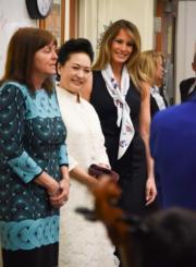 【第一夫人時裝】美國時間2017年4月7日,中國第一夫人彭麗媛 (中),由美國第一夫人梅拉尼婭 (右) 陪同探訪美國一間學校。 (法新社)