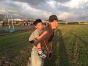 范范背起飛飛在球場到處走。