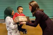 【英國王室】英國劍橋公爵夫人凱特(右)向小朋友送聖誕禮物。(Kensington Palace Twitter圖片)