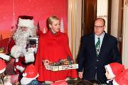 【摩納哥王室】摩納哥王妃維特斯托克(中)與阿爾貝二世親王(右)向小朋友派聖誕禮物。(法新社)