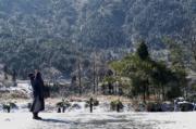 一名僧人在黃柏山國家森林公園內拍攝雪景。(新華社)