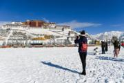 2018年12月19日,遊客在布達拉宮廣場上拍攝雪景。(新華社)