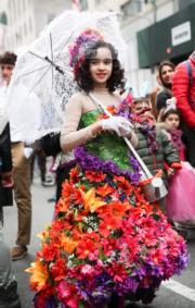 【復活節花帽巡遊——紐約】一名女孩戴上花帽配花裙參與活動。(新華社)