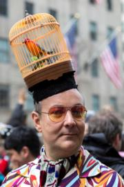 【復活節花帽巡遊——紐約】一名男子戴上鳥籠造型帽子。(新華社)