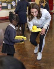 2018年1月17日,英國劍橋公爵夫人凱特身到訪學校,與女生練習球類活動。(法新社)