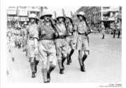 【香港百年蛻變】1940年港府宣布香港進入非常時期,徵集英僑入伍。照片中為香港義勇軍在灣仔修頓球場外步操,攝於1940年。(圖片及資料由饒宗頤文化館提供)