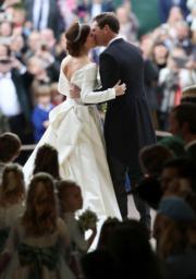 2018年10月12日,英國尤金妮亞公主(左)與Jack Brooksbank(右)在溫莎堡聖喬治教堂舉行婚禮,一對新人在教堂前親吻。(法新社)