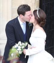2018年10月12日,英國尤金妮亞公主(右)與Jack Brooksbank(左)舉行婚禮,二人在教堂前深情一吻。(法新社)