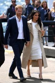 2018年10月16日,懷孕的梅根(右)偕哈里王子(左)外訪澳洲,二人十指緊扣。(法新社)