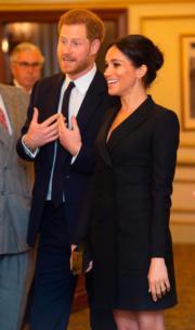 2018年8月29日,梅根(右)穿上加拿大Judith & Charles的黑色連身短裙,與哈里王子(左)出席活動。(法新社)