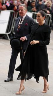2019年1月31日,梅根(右)在倫敦出席活動,穿上Givenchy黑色大衣內襯同色裙子,配裸色斗零高踭鞋。(法新社)