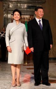 2019年3月22日,中國國家主席習近平(右)與夫人彭麗媛(左)外訪意大利。彭麗媛穿上及膝連身裙配白色clutch。(法新社)