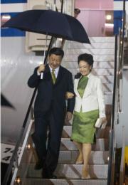 2013年,國家主席習近平(左)與夫人彭麗媛(右)乘坐專機抵達特立尼達和多巴哥首都西班牙港。習近平佩戴綠色領呔,彭麗媛則穿綠色旗袍。(新華社資料圖片)