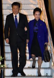 2015年10月,習近平(左)與夫人彭麗媛(右)抵達英國倫敦。彭麗媛身穿一襲中式旗袍、外套藍色大衣,習近平則佩戴藍色領帶。(法新社資料圖片)