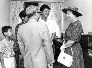 【1986年再度訪港】英女王(右)探訪敬心閣的居民,當時的房屋署長彭玉陸(前排左)當翻譯。(政府新聞處資料圖片)