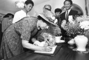 【1986年再度訪港】英女王前往沙田隆亨邨探訪,並在紀念特刊上簽名留念。(政府新聞處資料圖片)