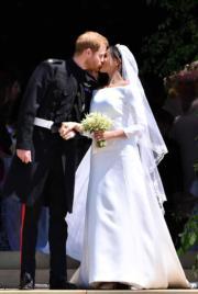 英國哈里王子(左)與梅根(右)5月19日舉行婚禮,儀式後,二人在教堂門前親吻。(法新社)