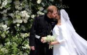 2018年5月19日,英國哈里王子(左)與梅根(右)結婚,新人深情一吻。(法新社)